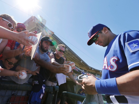 Russell Wilson signs autographs before the start of a Cactus League baseball game between the Texas Rangers and the Cleveland Indians in Surprise, Ariz.
