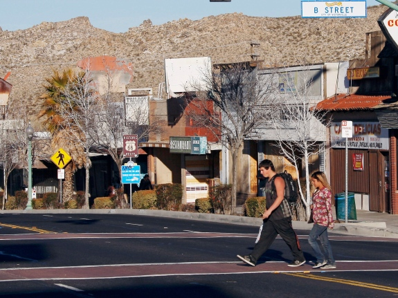 In this Jan. 25, 2012, photo, people walk in the Old Town section of Victorville, Calif., where most stores are vacant or boarded up.