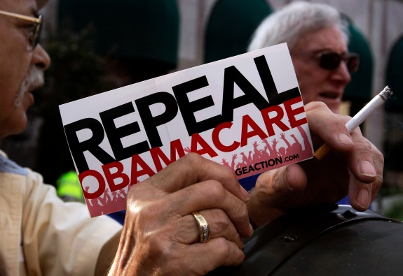 "A small group of demonstrators stand outside of the HIlton Hotel and Suites prior to former South Carolina Senator DeMint, president of the The Heritage Foundation, speaking at a ""Defund Obamacare Tour"" rally in Indianapolis"