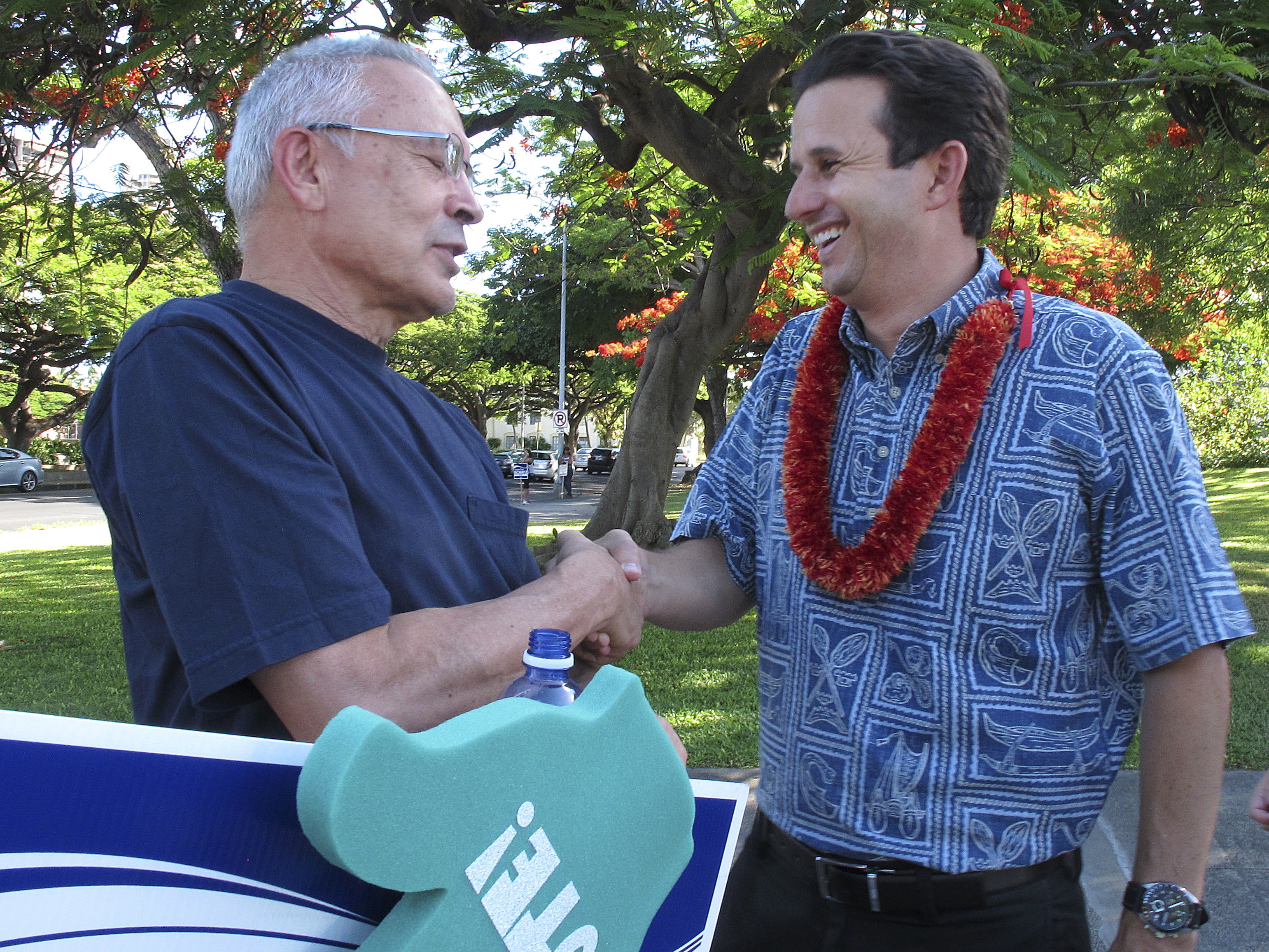 U.S. Sen. Brian Schatz, right, greets a supporter during a campaign event in Honolulu in July.