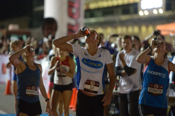 Members of the Women's Elite race chug beers at the starting line of the Flotrack Beer Mile World Championships in Austin