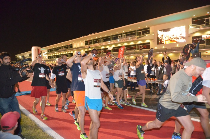 Athletes competing in the open heat of the Flotrack Beer Mile World Championship crack open their first beers at Circuit of the Americas in Austin