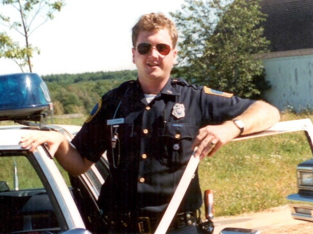 A photo of Stinson from summer 1986 when he was a police officer in Dover, New Hampshire. Taken in Dover, New Hampshire, outside his cruiser.