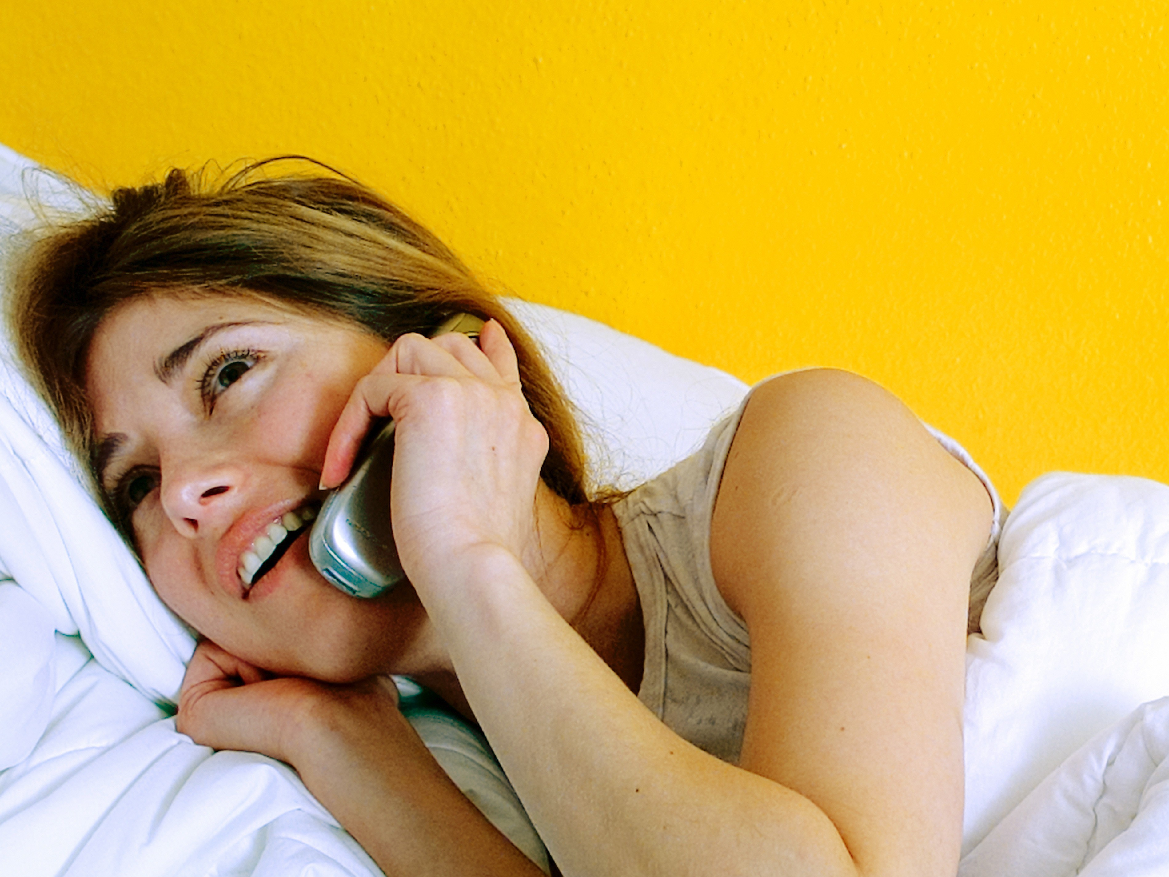 Frau mit Handy im Bett – lady with a mobile in the bed
