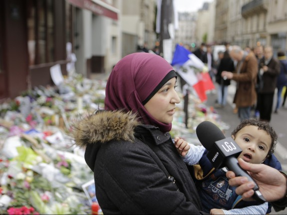 A muslim woman is interviewed at the memorial outside the
