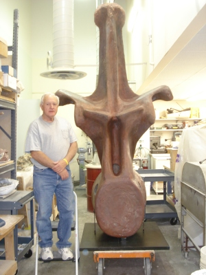Tony DiCroce, a volunteer who helped Ken Carpenter build his replica of an Amphicoelias fragillimus vertebrae, standing next to the replica.