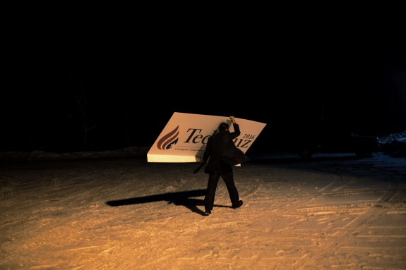 A man carries a newly acquired sign to his vehicle following the final stop of the day on Ted Cruz's bus tour. Whitefield, New Hampshire. January 18, 2016.