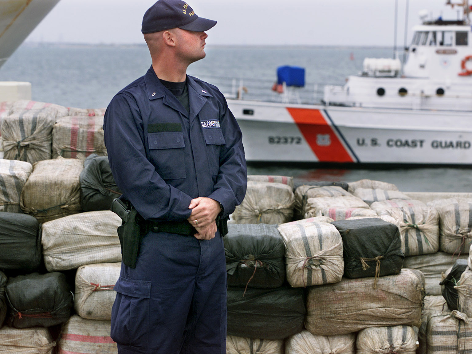 San Diego––An armed member of the U.S.Coast Gaurd and ship keep an eye on some of the 12 metric tons