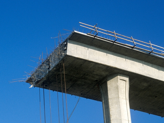 A concrete freeway structure ends abruptly with iron support structures sticking out and safety rails lining the top edge until further construction is continued, USA