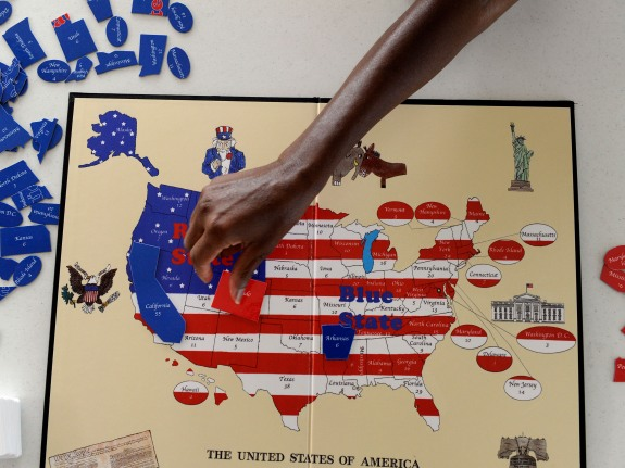 Sherri Pollard, places a game piece on the Red State Blue State political board game created by her 13-year-old son, Tyler Pollard from Ft. Collins. The game was created by Tyler at age six and teaches U.S. geography, American history and the electoral co
