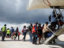 People wait in line to get in a Delta airplane at the Leonard M. Thompson International Airport  during an evacuation operation after Hurricane Dorian hit the Abaco Islands in Marsh Harbour