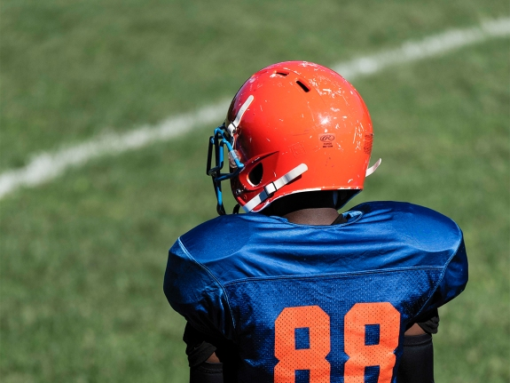 Young boy on the sideline of a Pop Warner football game