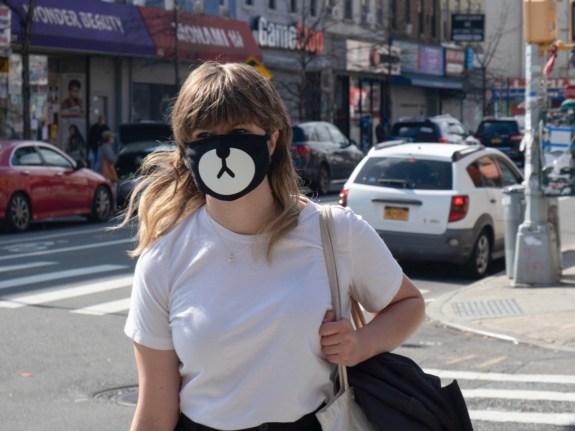 A young woman wearing a facemask walking down Knickerbocker