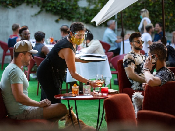 People have drinks and dine at the outdoor patio at La Boheme in West Hollywood as coronavirus surges