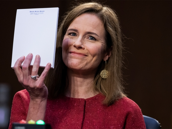 Amy Coney Barrett at hearing holding up a pad of paper