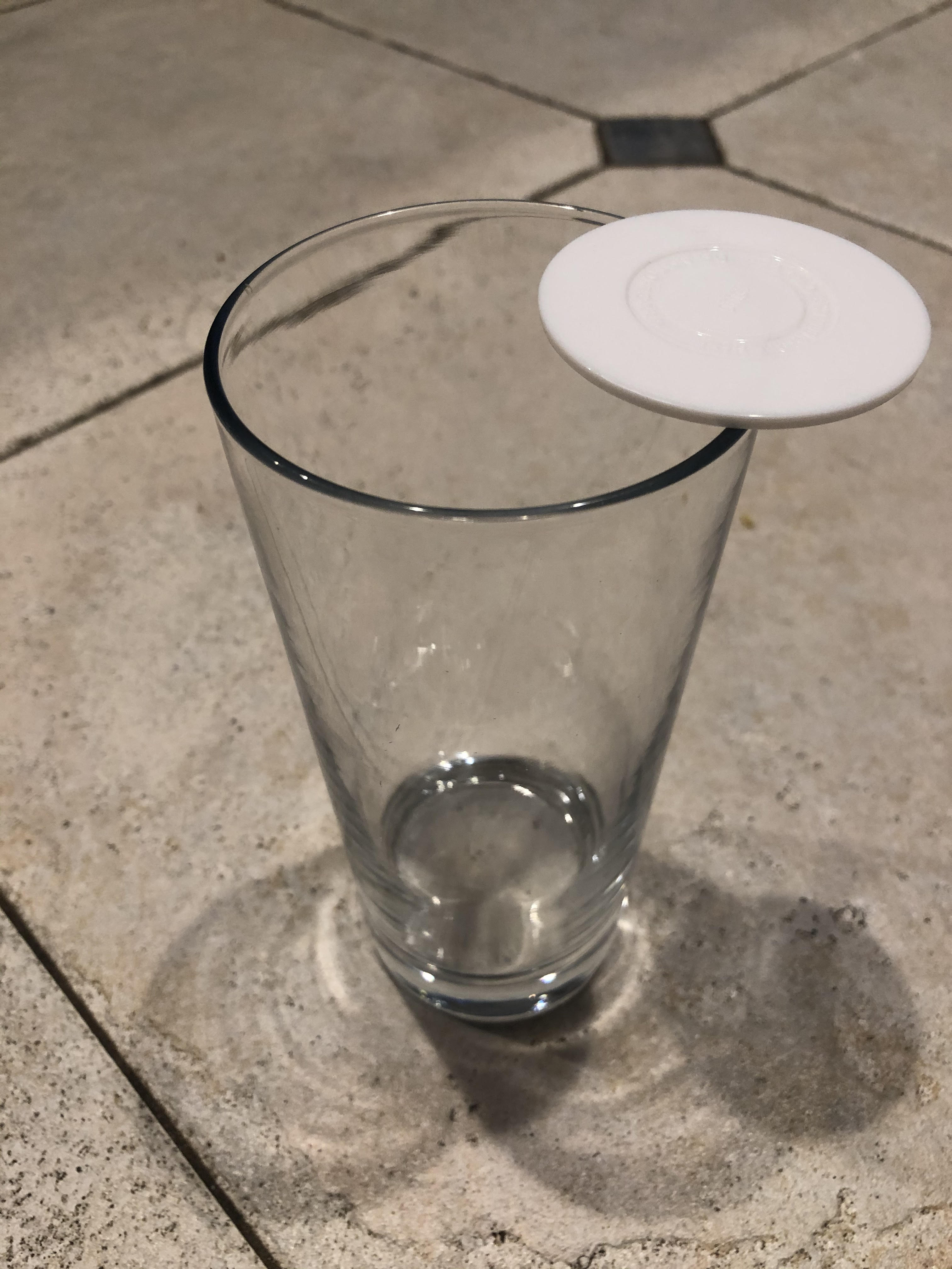 glass cup with a white disk balancing on its edge