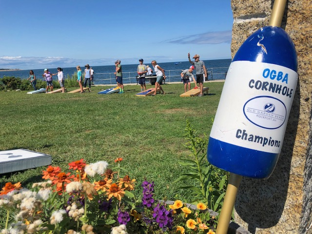 Photo of 2019 OGBA Cornhole Championships. In the background, people are playing cornhole along a coastline.