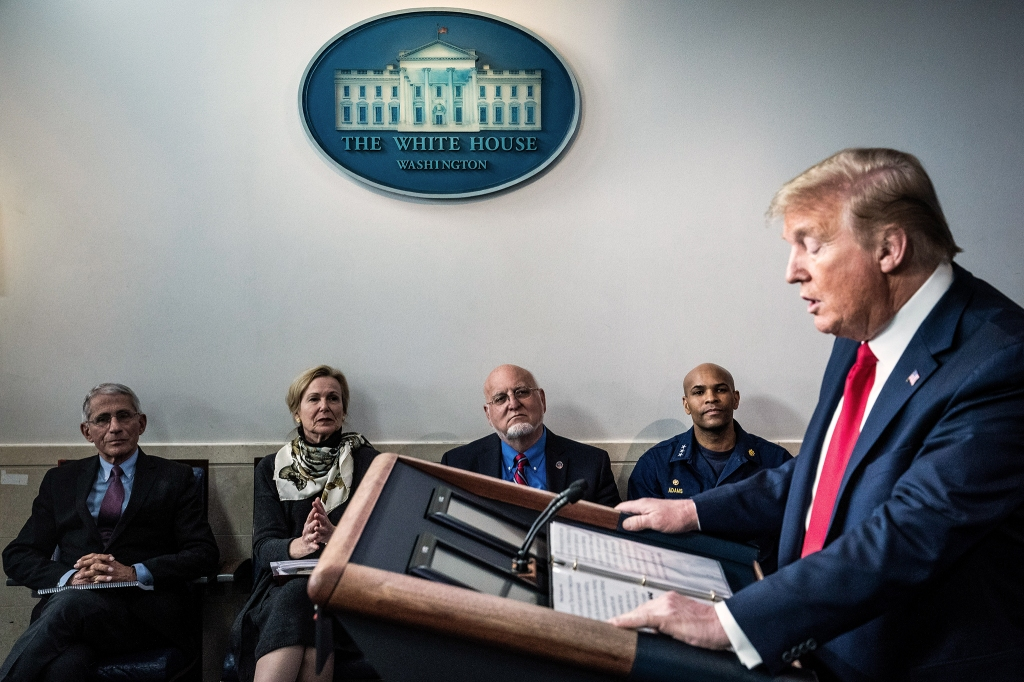 Dr. Anthony Fauci, director of the National Institute of Allergy and Infectious Diseases, Dr. Deborah Birx, White House coronavirus response coordinator, Dr. Robert Redfield, director of the Centers for Disease Control and Prevention, and U.S. Surgeon General Jerome Adams listen as President Donald J. Trump speaks during a COVID-19 briefing.