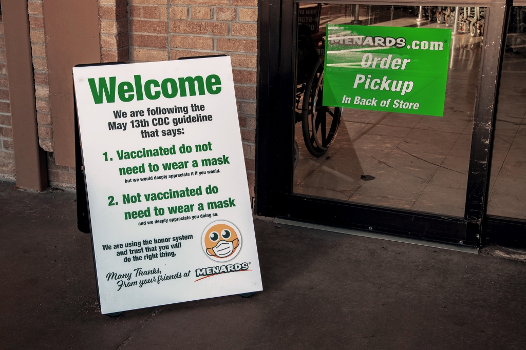 Welcome sign at a hardware store with new mask guidelines for vaccinated and unvaccinated shoppers.