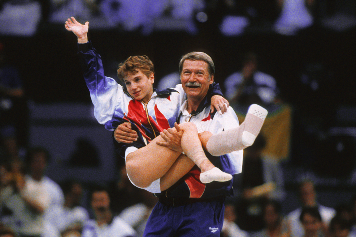 Béla Károlyi carrying American gymnast Kerri Strug