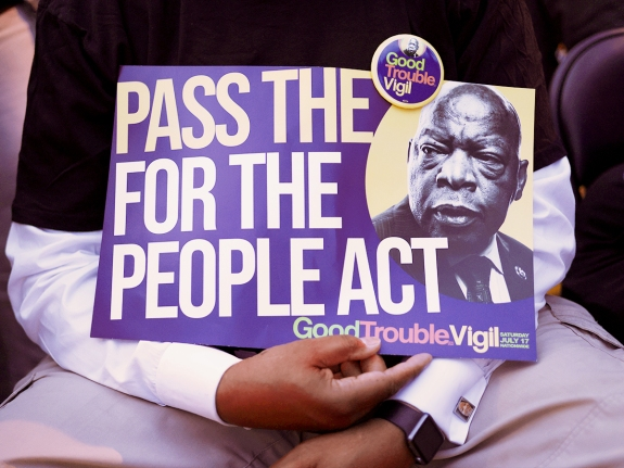 """A voting rights activist holds a sign that reads """"Pass The For The People Act"""""""