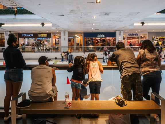 A family watches people ice skate at a mall in Houston, Texas
