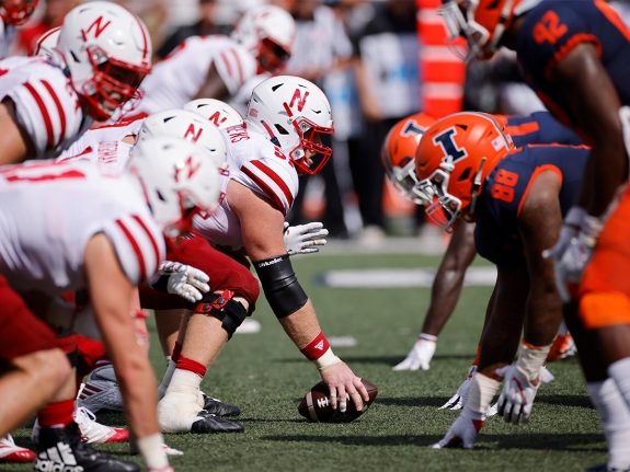 Nebraska Cornhuskers and Illinois Fighting Illini players face off at the line of scrimmage