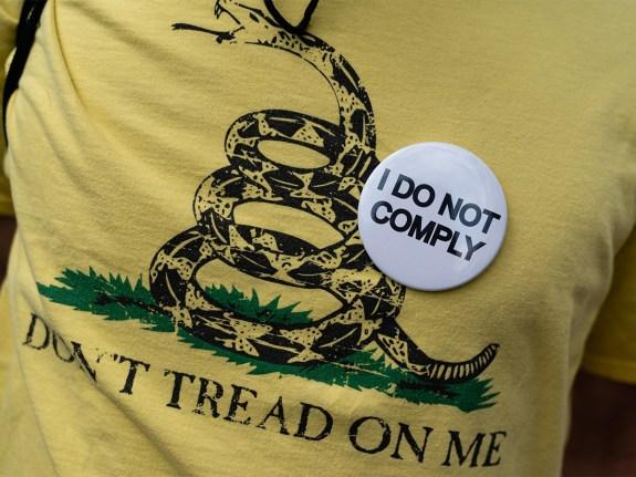 A man wears a 'I Do Not Comply' pin on a 'Don't Tread On Me' shirt
