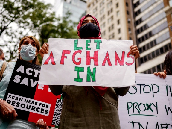 """A demonstrator holds a sign that reads """"Let Afghans In"""""""