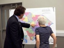 Two people look over a map of the current South Carolina Senate districts.