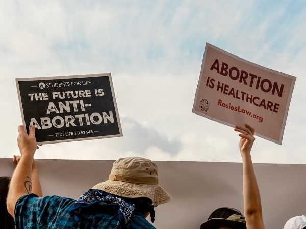Demonstrators hold pro-life and pro-choice signs