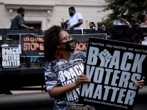 """Demonstrators in Washington, DC hold up signs that read """"Black Voters Matter"""""""